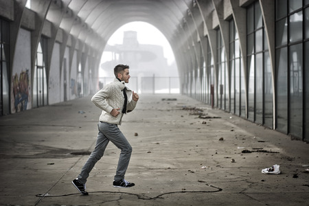 stride: Side View of Young Man Running Through Abandoned Arched Tunnel