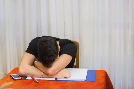 unmotivated: Tired, exhausted or despondent young man sitting at a table with a folder of paperwork leaning forwards with his head on his arms Stock Photo