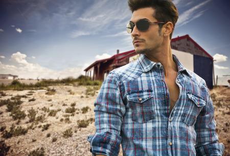 gafas de sol: Apuesto hombre de moda en gafas de sol y una camisa a cuadros azul posando al aire libre con una caba�a de madera detr�s y mirando copyspace en el centro de la imagen