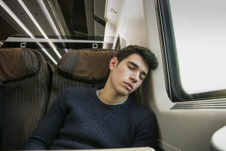 Young man sleeping while traveling on a train sitting in a passenger coach with his head resting on his hand and eyes closed Stock Photo