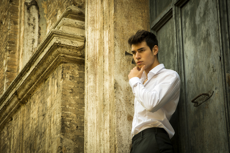 Elegant young man leaning against old wall and door, shot from below photo