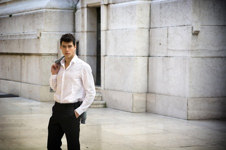 Handsome elegant young businessman outdoor, marble wall and ground looking at camera photo