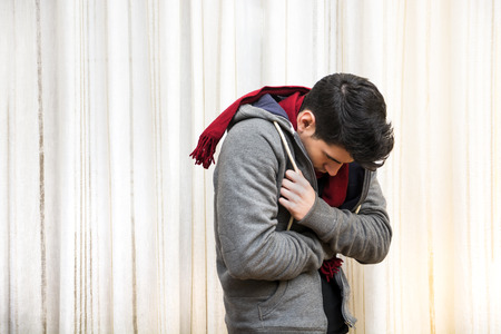 Young man feeling very cold, curling up inside his heavy sweater, wearing a red scarf Stockfoto