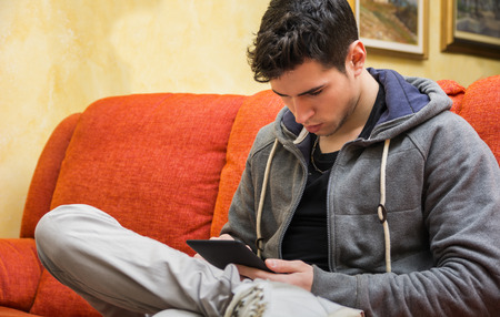 Handsome young man at home reading with ebook reader sitting on a couch photo