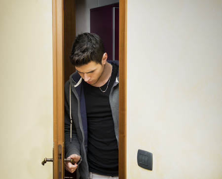 doorways: Handsome young man opening door to enter into a room, looking down at handle