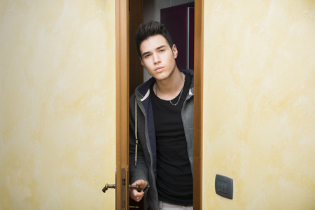 apertura: Joven puerta de apertura Hermoso hombre para entrar en una habitaci�n, mirando a la c�mara