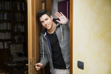 out door: Smiling young man getting out of door waving at the camera with a friendly cheerful smile as he peers around the edge of a wooden door Stock Photo