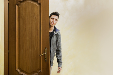 Handsome young man behind open door, getting out, looking at camera with friendly expression