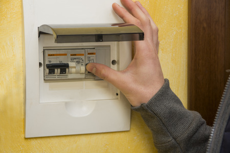 activating: Close up of male hand using an electronic control panel, to switch on electricity at home