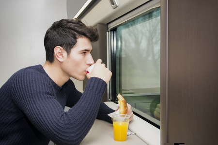refreshments: Young man eating refreshments on a train balancing the fruit juice on the ledge below the window as he eats a roll and coffee while commuting or traveling Stock Photo