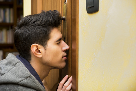 peeping: Young man spying through the keyhole of a door standing with his eye pressed up against the wood as he tries to see what is going on inside