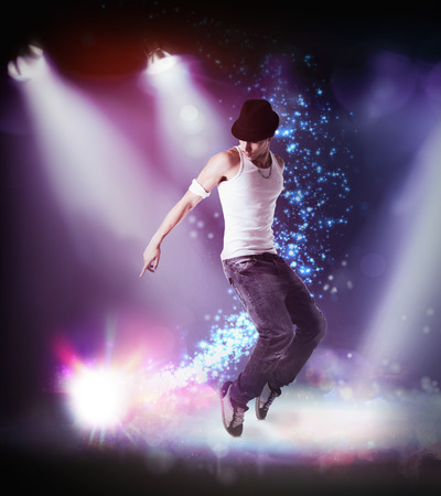 breakdancing: Trendy young man in hat hip hop dancing, breakdancing on a stage, in the beams of three spotlights leaping in the air with bent knees