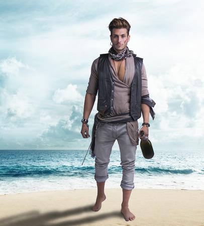 pies descalzos: Joven pirata hermoso en la playa, descalzo, sosteniendo la botella de vino, mirando a la c�mara