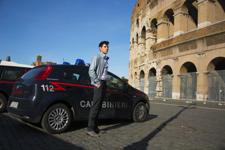 patrol car: Handsome trendy young Italian Carabiniere standing alongside a patrol car parked outside the Colosseum in Rome, Italy watching something off frame to the right Editorial