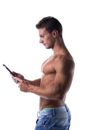 e book reader: Shirtless young male bodybuiler holding ebook reader or tablet PC standing isolated on white background