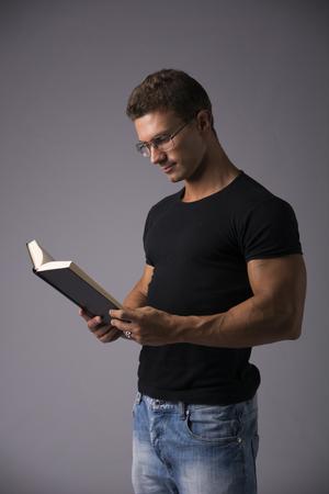 hombre rojo: Handsome muscular atractivo hombre lee el libro grande sobre fondo gris, con gafas Foto de archivo