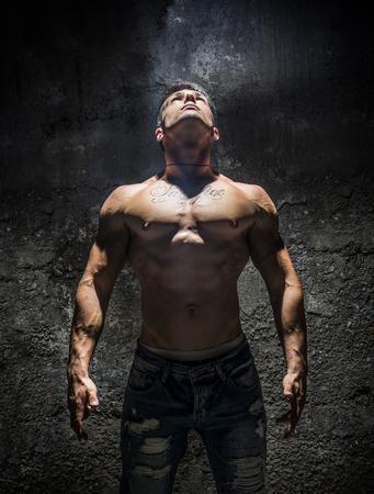 Shirtless Muscle Man Looking Up Into Bright Overhead Light Illuminating Him Like a Superhero