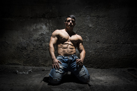 Muscular shirtless young man on his knees with light above head in grunge, vintage place