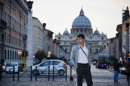 italian people: Young man standing in front of St. Peters Square in Vatican City, with cathedrals dome in the distance