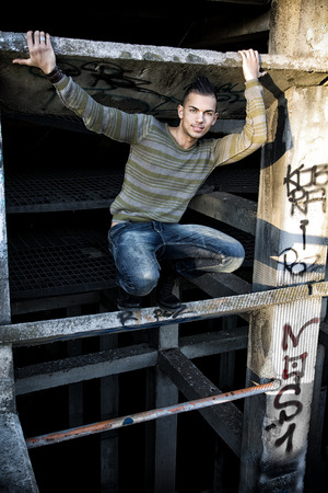 spanish looking: Handsome smiling young man in abandoned industrial site outdoor looking at camera Stock Photo