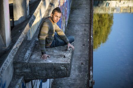 spanish looking: Handsome young man on concrete structure in abandoned industrial site