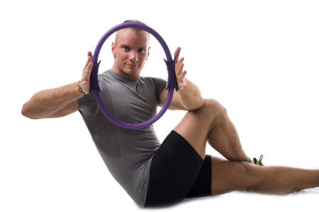 pilates studio: Attractive athletic young man working out with pilates ring on white background, looking at camera Stock Photo