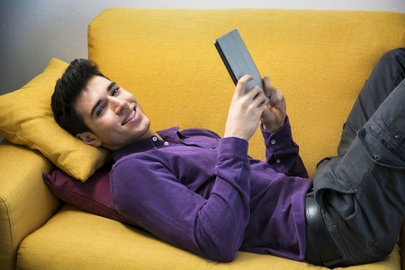 Attractive young man using tablet PC while laying on couch, smiling at camera photo