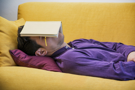 Over-worked, tired young man at home sleeping instead of working or studying, resting with head covered by open book Stok Fotoğraf