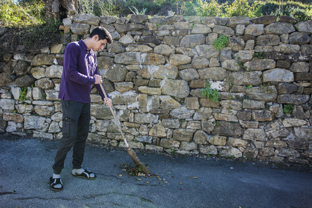 groundskeeper: Handsome  young man outdoor in rural road sweeping foliage with broom Stock Photo