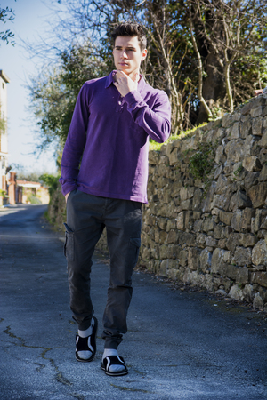 loafers: Handsome young man walking along rural road with loafers, looking confident and relaxed