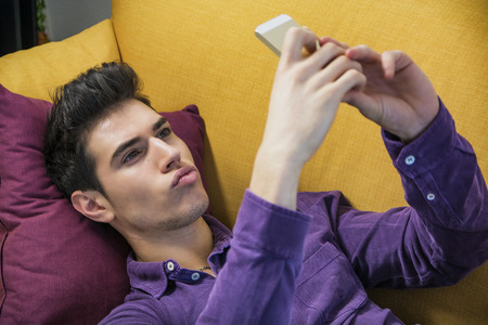 sexy pictures: Sexy handsome young man sitting indoors posing for a selfie on his mobile phone pouting his lips seductively with a serious expression