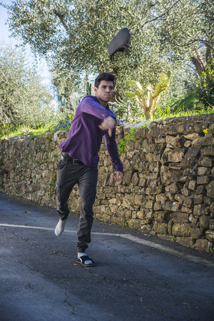 irked: Angry young man standing in the middle of a rural road with a stone wall tossing his shoe through the air towards the camera
