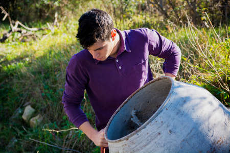 looking aside: Handsome young man working with a cement mixer looking aside as he tilts the drum in a renovation or construction concept, high angle against long green grass