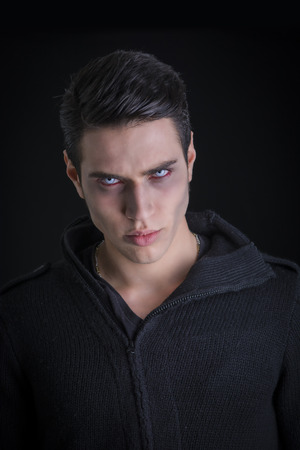 vampire teeth: Portrait of a Young Vampire Man with Black Sweater, Looking at the Camera, on a Dark Smoky Background. Stock Photo