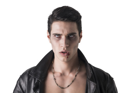 Portrait of a Young Vampire Man in an Open Black Leather Jacket, Looking at the Camera, on a White Background. Stock Photo