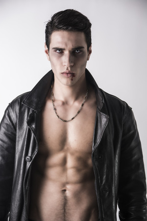 fangs: Portrait of a Young Vampire Man in an Open Black Leather Jacket, Showing his Chest and Abs, Looking at the Camera, on a White Background.
