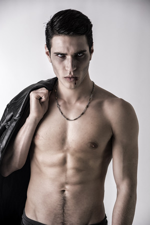 fangs: Portrait of a Young Vampire Man with Black Leather Jacket, Showing his Torso,  Chest and Abs, Looking at the Camera, on a White Background. Stock Photo