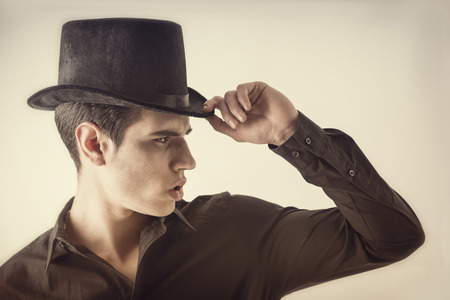 Portrait of a Young Vampire Man with Black Shirt and Top Hat, Tipping his Hat, looking to right photo