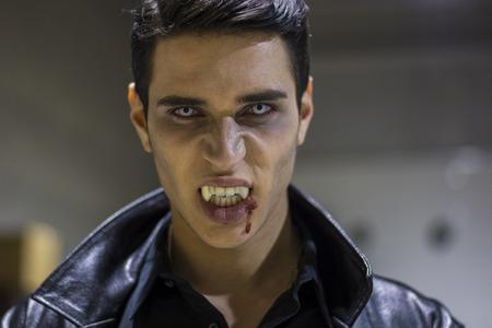 カメラを見て、彼の口に血で、革の衣類のハンサムなヴァンパイア男の顔を閉じます。