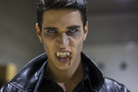 mouth close up: Close up Face of a Handsome Vampire Man in Leather Clothing, with Blood on his Mouth, Looking at the Camera.