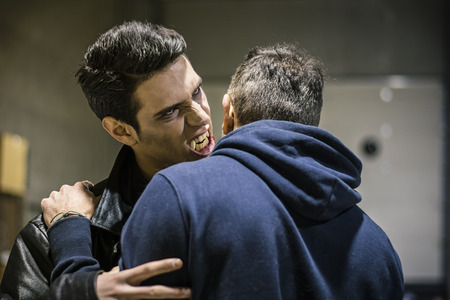 brute: Close up Hungry Young Male Vampire with Scary Facial Expression Bites the Neck While Holding a Man