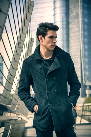 Stylish Young Handsome Man in Black Coat Standing in City Center Street with Skyscraper Behind Him, Looking to the Right of the Frame. photo