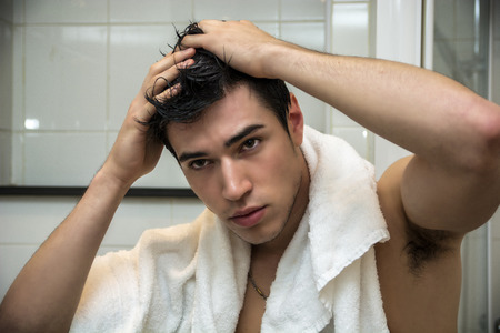 Close up Gorgeous Young Man after his Showers with White Towel on His Shoulders Holding his Head. Stock Photo