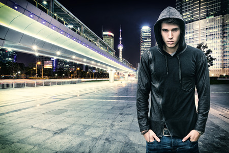 hooded shirt: Gorgeous Young Man in Trendy Hooded Shirt Standing at the City Street While Looking at the Camera.