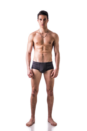topless: Full length body shot of handsome, fit young man wearing only underwear standing isolated on white background, looking at camera Stock Photo
