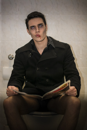 Scary Young Male Vampire in Black Coat Sitting on a Toilet with Magazine and Looking at the Camera.
