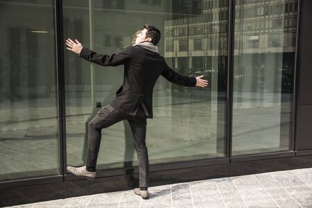 peering: Well Dressed Man with Outstretched Arms Leaning or Plastered Against Window of Office Building as if Peering Inside Stock Photo