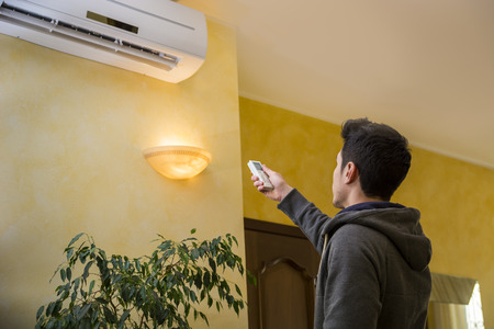 Young man switching on or adjusting the wall mounted air conditioner in the living room with a remote control