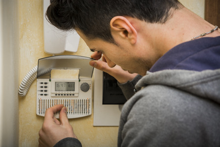 readout: Over the shoulder close up view of a young man standing checking the speaker phone or intercom and alarm system at his apartment or house displaying the keypad and digital readout