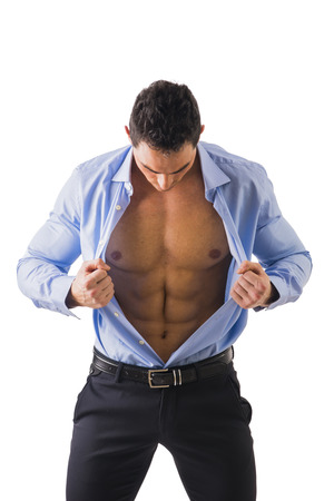 open shirt: Young man displaying his abdominal muscles holding open his stylish blue shirt with his hands while looking down, isolated on white